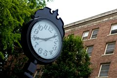 Outdoor clock in front of a brick wall stock image