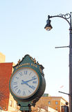 Outdoor clock with roman numerals and light pole Pittsfield,MA Royalty Free Stock Images