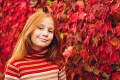 Outdoor portrait of cute preteen girl. Outdoor close up portrait of adorable preteen girl of 10 years old, leaning on red ivy wall. Child with long red hair Royalty Free Stock Image