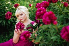 Outdoor close up portrait of beautiful young woman in the blooming garden. Female spring fashion concept royalty free stock photo
