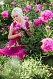 Outdoor close up portrait of beautiful young woman in the blooming garden. Female spring fashion concept stock image