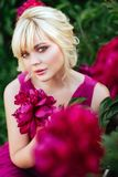 Outdoor close up portrait of beautiful young woman in the blooming garden. Female spring fashion concept stock photography