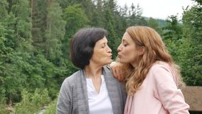 Outdoor close up portrait of smiling happy caucasian senior mother with her adult daughter hugging and looking at the stock video