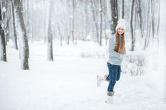 Outdoor close-up portrait of young beautiful happy smiling girl, wearing stylish knitted winter hat and gloves. A girl running thr Royalty Free Stock Photos