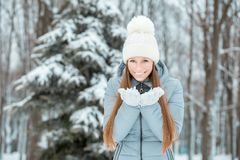 Outdoor close-up portrait of young beautiful happy smiling girl, wearing stylish knitted winter hat and gloves. Model expressing j Stock Image