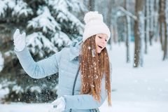 Outdoor close-up portrait of young beautiful happy smiling girl, wearing stylish knitted winter hat and gloves. Model expressing j Royalty Free Stock Photo