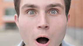 Outdoor close up of wondering young man face stock video footage