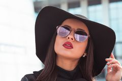 Outdoor closeup portrait of beautiful model in fashionable black. Outdoor closeup portrait of beautiful woman in fashionable black coat and stylish hat.Female Royalty Free Stock Photography