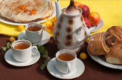 An outdoor composition with tea cups, a tea pot, a plate of pancakes, pastry, ripe fruit and field flowers on a bright table cloth Royalty Free Stock Photography