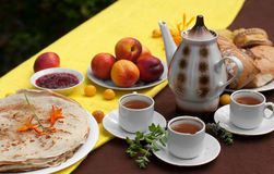 An outdoor composition with tea cups, a tea pot, a plate of pancakes, pastry, ripe fruit and field flowers on a bright table cloth Stock Photo