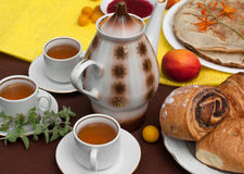 An outdoor composition with tea cups, a tea pot, a plate of pancakes, pastry, ripe fruit and field flowers on a bright table cloth Stock Images