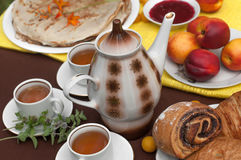 An outdoor composition with tea cups, a tea pot, a plate of pancakes, pastry, ripe fruit and field flowers on a bright table cloth Royalty Free Stock Image