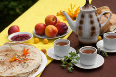 An outdoor composition with tea cups, a tea pot, a plate of pancakes, pastry, ripe fruit and field flowers on a bright table cloth Stock Image