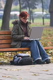 Outdoor computer work. Redhead girl working on a laptop in an autumn park.Shot with Canon 70-200mm f/2.8L IS USM Royalty Free Stock Photos