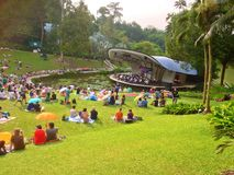 Outdoor concert - Botanic Gardens, Singapore. Picnickers sitting and relaxing on the grass and listening to the symphony orchestra playing music on stage by the royalty free stock image