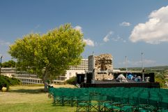 Outdoor concert stage. Tree in shape of tree. A tree in shape of a heart near to a concert stage and green chairs Stock Photos