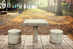 Outdoor concrete chess table in a public park. Outdoor concrete chess table and two seats in a public park in Montreal, Canada stock photo