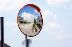 Outdoor convex safety mirror hanging on wall with reflection of an urban roadside view of cars parked along the street. By residential apartment buildings stock images
