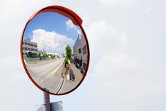 Outdoor convex safety mirror hanging on wall with reflection of an urban roadside view of cars parked along the street. By residential apartment buildings stock image