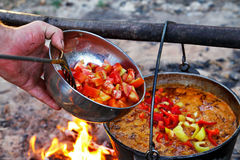 Outdoor cooking. Making soupe on a fire in a pot Stock Photo