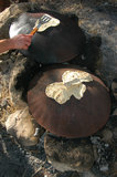 Outdoor Cooking Of Pita Bread. A metal round plate on fire camp for cooking pita bread in the middle east. Some one with a kitchen spoon flips the pita's cooking stock photos