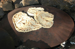 Outdoor Cooking Of Pita Bread. A metal round plate on fire camp for cooking pita bread in the middle east Stock Images