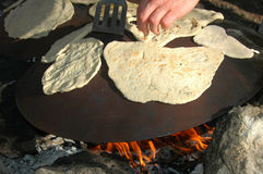 Outdoor Cooking Of Pita Bread. A metal round plate on fire camp for cooking pita bread in the middle east. Some one with a kitchen spoon flips the pita's cooking stock images