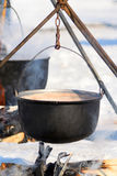 Outdoor Cooking in Winter. With a small black couldron above burning firewood Stock Image