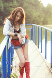 Outdoor country styled portrait of beautiful woman. Beautiful woman in shorts and red high boots on a bridge; country styled portrait royalty free stock image