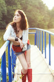 Outdoor country styled portrait of beautiful woman. Beautiful woman in shorts and red high boots on a bridge; country styled portrait stock photo