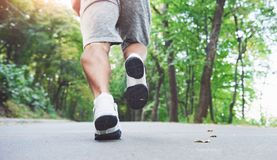 Outdoor cross-country running in concept for exercising, fitness and healthy lifestyle. Close up of feet of young runner. Man running along road in the park royalty free stock image