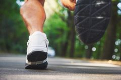 Outdoor cross-country running in concept for exercising, fitness and healthy lifestyle. Close up of feet of young runner. Man running along road in the park royalty free stock photo