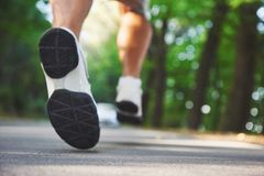 Outdoor cross-country running in concept for exercising, fitness and healthy lifestyle. Close up of feet of young runner. Man running along road in the park stock images