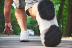 Outdoor cross-country running in concept for exercising, fitness and healthy lifestyle. Close up of feet of young runner. Man running along road in the park royalty free stock photography