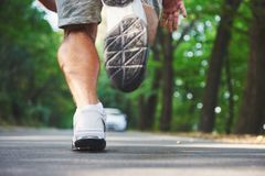 Outdoor cross-country running in concept for exercising, fitness and healthy lifestyle. Close up of feet of young runner. Man running along road in the park stock photography