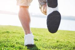 Outdoor cross-country running in summer sunshine concept for exercising, fitness and healthy lifestyle. Close up of feet. Of a man running in grass Stock Photography