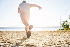 Outdoor cross-country running in summer sunshine concept for exercising, fitness and healthy lifestyle. Close up of feet. Of a man running in grass. Shallow Stock Photography