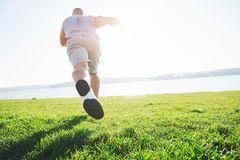 Outdoor cross-country running in summer sunshine concept for exercising, fitness and healthy lifestyle. Close up of feet. Of a man running in grass. Shallow Royalty Free Stock Images