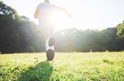 Outdoor cross-country running in summer sunshine concept for exercising, fitness and healthy lifestyle. Close up of feet. Of a man running in grass. Shallow Royalty Free Stock Image
