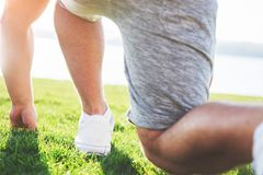 Outdoor cross-country running in summer sunshine concept for exercising, fitness and healthy lifestyle. Close up of feet. Of a man running in grass Stock Images