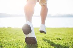 Outdoor cross-country running in summer sunshine concept for exercising, fitness and healthy lifestyle. Close up of feet. Of a man running in grass Royalty Free Stock Photo
