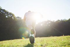Outdoor cross-country running in summer sunshine concept for exercising, fitness and healthy lifestyle. Close up of feet. Of a man running in grass Stock Photo