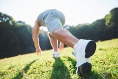 Outdoor cross-country running in summer sunshine concept for exercising, fitness and healthy lifestyle. Close up of feet. Of a man running in grass Stock Photos