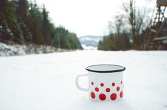 Outdoor cup of tea on a snow during a winter weather, Hot drinks. Natural background. Winter background covered by snow. Outdoor cup of tea on a snow during a Stock Photo