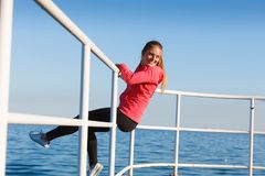 Woman sitting on handrail by the sea. Outdoor, dangerous play, freedom and sport concept. Woman in sports suit sitting on handrail next to sea stock photos