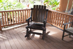 Outdoor dark wooden rocking chair in the garden royalty free stock photos