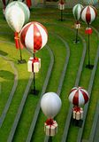 Outdoor decoration of the festive season with square shaped gift boxes hanging on the hot air balloons over the green lawn. Texture Background royalty free stock images