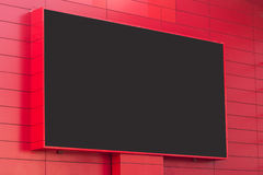 Outdoor digital display on red wall. Horizontal front view of outdoor digital display with blank screen on red building exterior wall Stock Photo