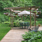 Outdoor dining area. Surrounded by hanging baskets of trailing flowers Royalty Free Stock Photo