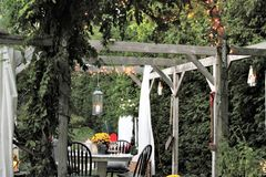 Outdoor dining area in the fall. Outdoor dining area with overhead arbour, greenery and lights in the fall season Royalty Free Stock Photography